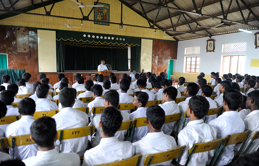 St. Patrick's College Rector Rev. Father Jerome Selvanayagam addressing the students during NCHS visit to St. Patrick's College to donate cricket gear.